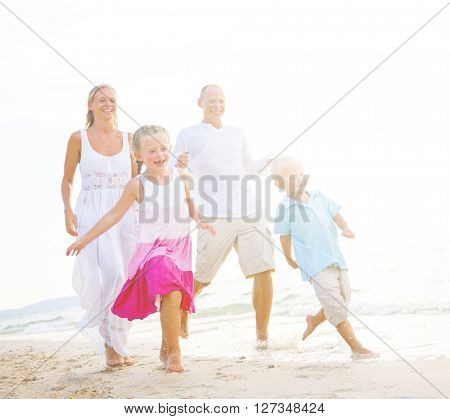 Family running on the beach.