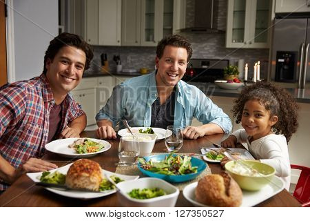 Male couple and black daughter dining at home look to camera