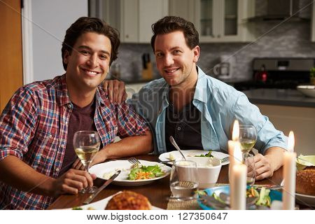 Male gay couple at home for a romantic dinner look to camera