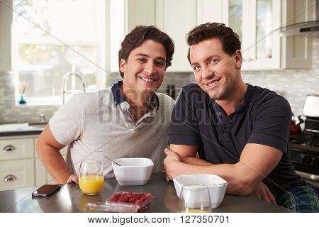 Male gay couple having breakfast in kitchen look to camera
