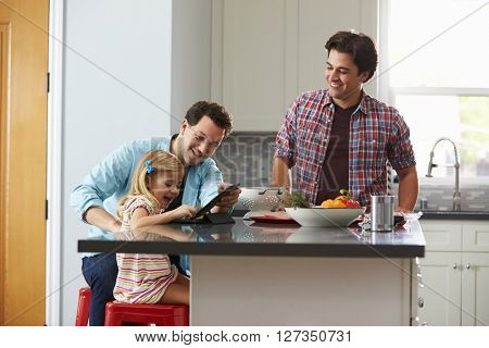 Girl using tablet computer in kitchen with her male parents