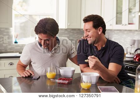Male gay couple looking at smartphone over breakfast