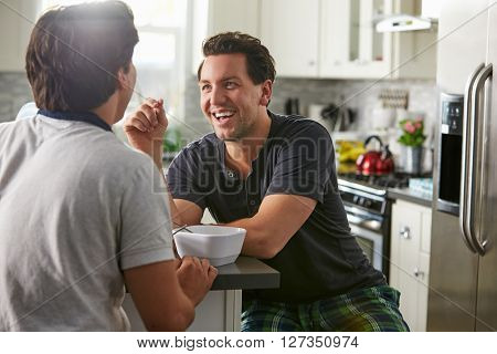 Male gay couple in their 20s talk in their kitchen, close up