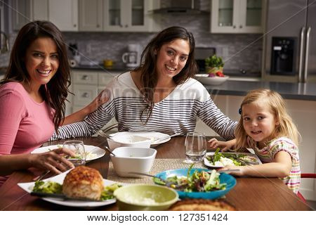 Female gay couple and daughter dining at home look to camera