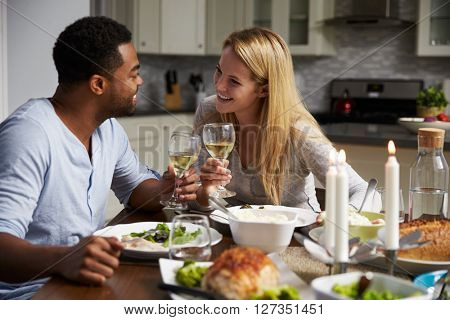 Romantic mixed race couple making a toast at meal in kitchen