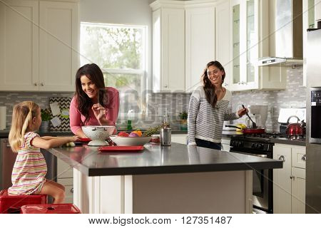 Girl with her female parents, preparing meal in the kitchen
