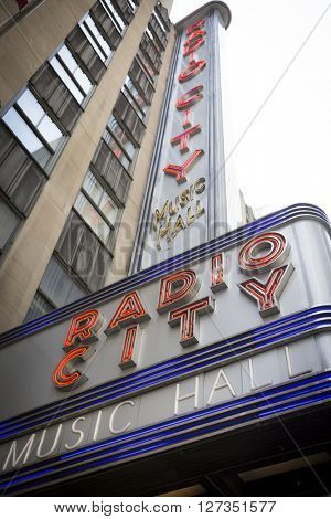 NEW YORK - 27 MAR 2016: Low angle view of the iconic Radio City Music Hall neon sign above the entrance in Manhattan on March 27, 2016. The theater hosts the Christmas Spectacular with the Rockettes.