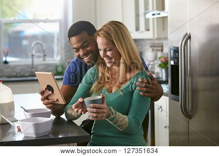 Mixed race couple looking at a tablet computer together in kitchen