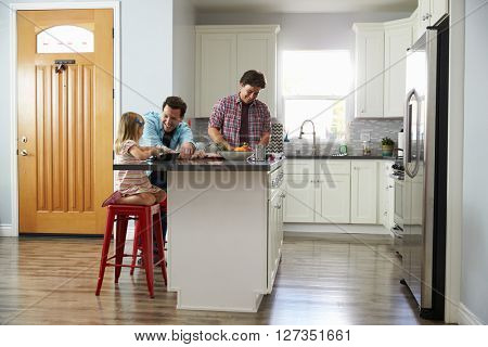 Male couple preparing a meal talk to their daughter in kitchen