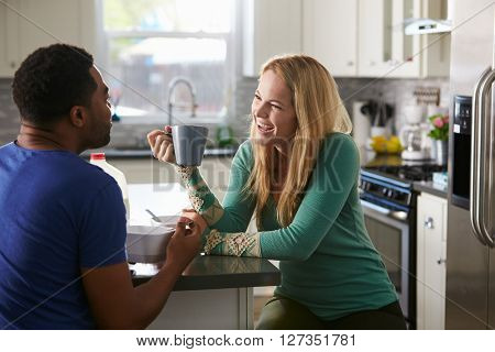 Mixed race couple talking over breakfast in the kitchen