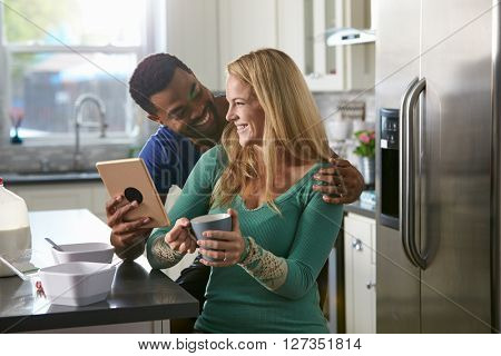 Mixed race couple using a tablet computer look at each other