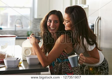 Gay female couple in their 20s embracing in  in the kitchen
