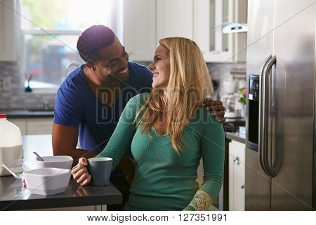Mixed race couple in kitchen look closely at each other