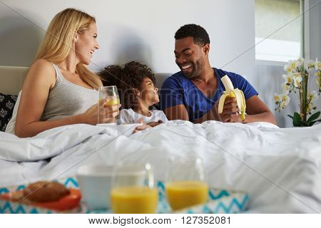 Mixed race couple and young daughter eating in bed together