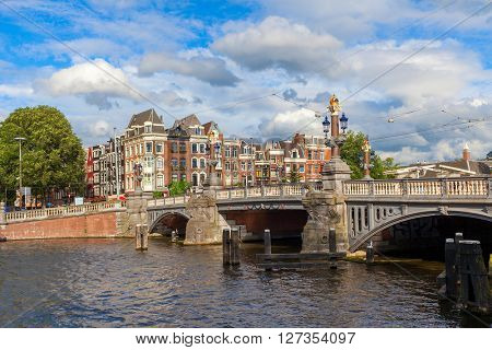 View of Blauwbrug Bridge and typical houses under beautiful sky in Amsterdam, Netherlands.