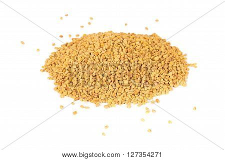 Unprocessed whole fenugreek (Trigonella foenum-graecumcumin) seeds heap over white background