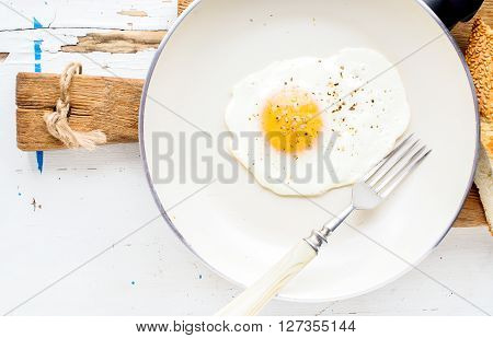 Fried egg with spice and bread slices in white ceramic frying pan on wooden board over white wooden background. Horizontal, copy space
