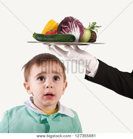 Boy looks at a plate of vegetables