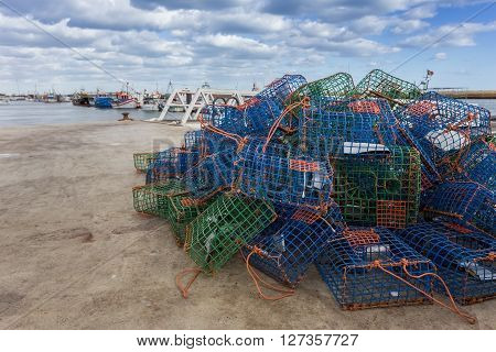 Traps for shellfish octopus on the dock. The ships in the background.