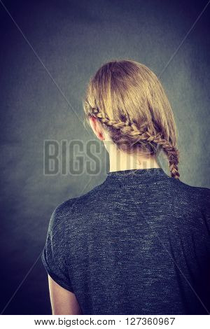 Hairstyle and hairdresser. Blonde woman head with braid tress plait. Back view of woman with beauty hairdo.