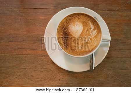 Hot coffee in white cup and saucer with silver spoon on wooden table in day time/ Hot coffee in white cup and saucer ** Note: Visible grain at 100%, best at smaller sizes
