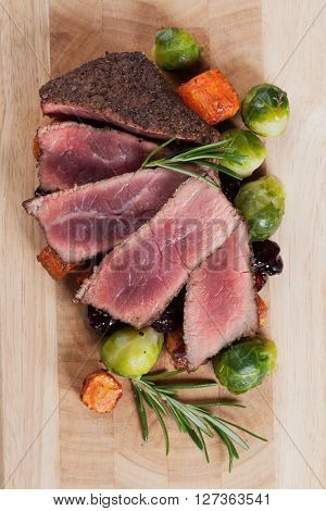 Rare beef steak cut in slices with carrot and brussel sprout
