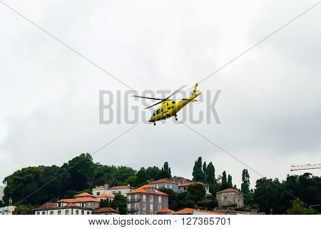 PORTO PORTUGAL - JUNE 18 2014: An INEM air ambulance helicopter takes off above the Douro river in overcast conditions. INEM is Portugal's national medical emergency institute.