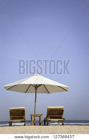 Tropical beach scenery with parasol and chairs