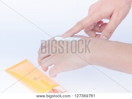 Woman pouring body lotion on hand on white background