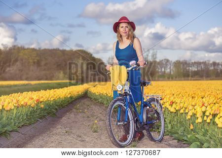 Cheerful woman walking with her bike through countryside - along yellow tulip fields