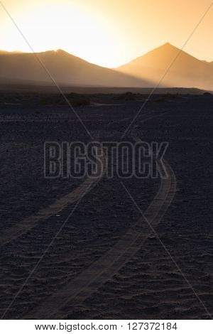 Car tire tracks in sand. Dirt road vanishing to the mountains sunlit in sunset. Copy space for text. Vertical composition.