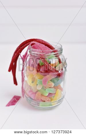 a glass jar full of different candies on a white surface