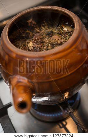 decocting medicinal herbs with enamel pot on gas burner