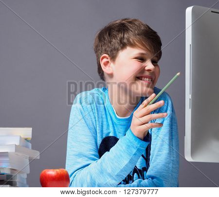Young happy boy learning on a computer at home