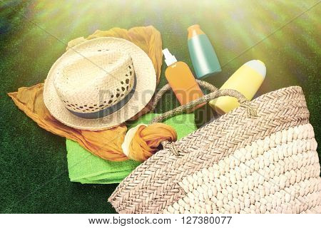 Wicker bag with scarf, hat and bottles of lotions on green background in sunlight. Retro style
