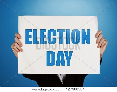Hands holding card with Election Day text on blue background