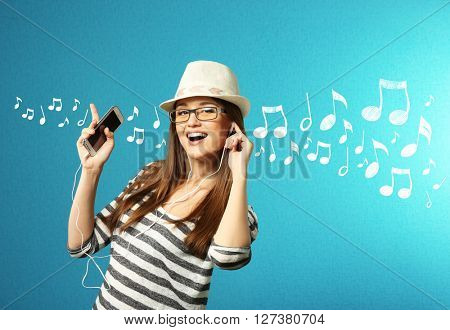 Young woman listens to music against turquoise background
