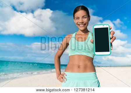 Asian runner girl using smartphone fitness app showing touchscreen for text copyspace. Happy athlete woman showing screen for weight loss progress following online video running workout on beach.