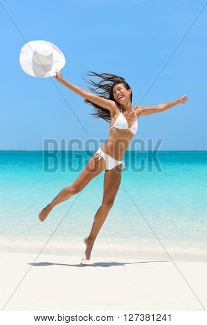 Happy joyful carefree girl jumping of joy on fun beach vacation getaway in tropical travel holiday destination. Happiness excitement, freedom, success in weight loss concept. Asian  bikini body woman.