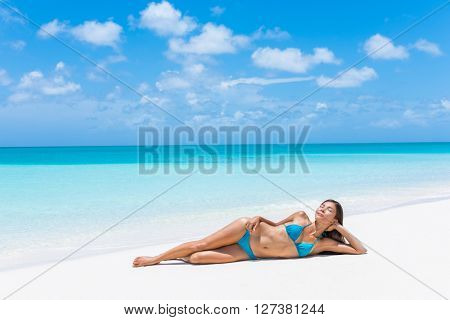 Sexy bikini woman relaxing with tanned slim body on beach vacation paradise getaway. Asian model lying down on perfect white sand sunbathing in tropical Caribbean travel destination. Luxury living.