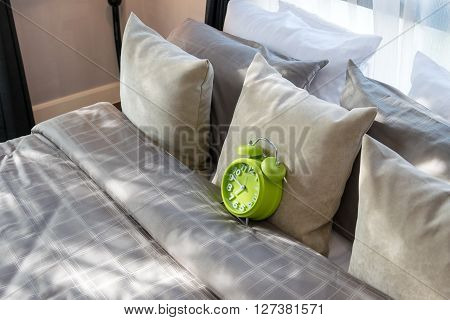 Modern Bedroom With Green Alarm Clock And Pillows On Bed
