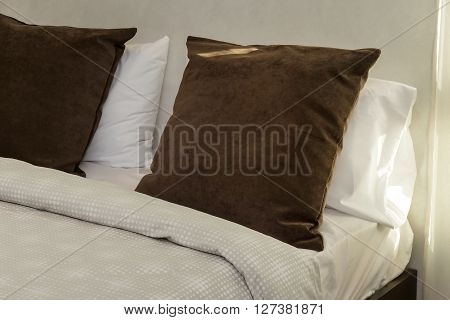 brown pillows on bed in modern bedroom
