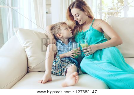 Mom with her son resting on the couch and drinking juice in living room
