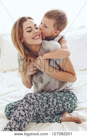 Young mother with her 6 years old little son dressed in pajamas are relaxing and playing in the bed at the weekend together, lazy morning. Son is kissing his mom.
