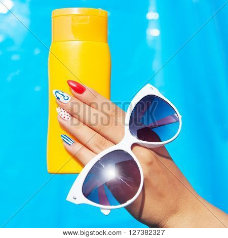 Summer fashion and beauty hand care concept, woman with marine sailor gel nails holding sunglasses and sunscreen lotion