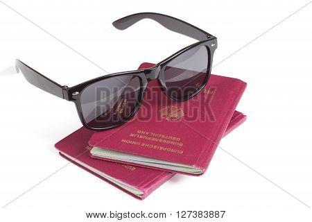 German travel passports and sunglasses over white