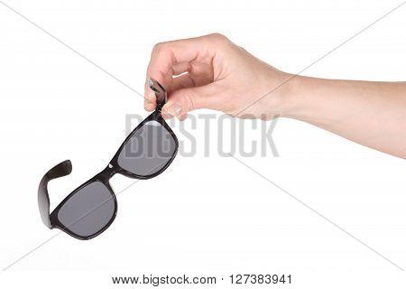 Female hand holding sunglasses over white background
