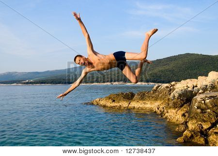 man jumping from rock in sea water and screaming AAA!