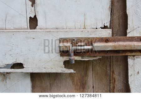 rusty bolt on decay white wooden door