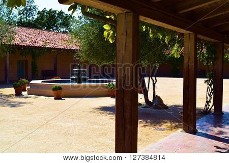 Spanish adobe style building with a water fountain in the courtyard